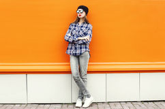 Manier mooie vrouw die een zwarte hoed, zonnebril en overhemd over kleurrijke sinaasappel dragen Royalty-vrije Stock Afbeeldingen