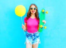 Manier mooie vrouw en gele luchtballon met skateboard die pret over kleurrijk blauw hebben Stock Fotografie