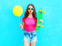 Manier mooie vrouw en gele luchtballon met skateboard over kleurrijk blauw Royalty-vrije Stock Afbeelding