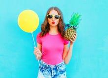 Manier mooie vrouw met gele luchtballon en ananas die een roze t-shirt over kleurrijk blauw dragen Stock Afbeelding