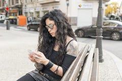 Manier mooie vrouw met slimme telefoonzitting op bank Royalty-vrije Stock Afbeelding
