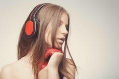 Manier neemt de mooie meisje het luisteren muziek met hoofdtelefoons, die rode handschoenen dragen, genoegen met lied Het concept royalty-vrije stock foto