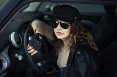 Manier openluchtfoto van vrouw met donker haar in zwart leerjasje en zonnebril die in retro auto stellen stock foto