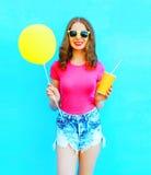 Manier vrij glimlachende jonge vrouw die een t-shirt, denimborrels met gele luchtballon en kop van vruchtensap over kleurrijk dra Royalty-vrije Stock Foto's