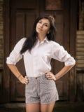Manier vrij jonge vrouw die openlucht dichtbijgelegen stellen een oude houten muur Royalty-vrije Stock Fotografie
