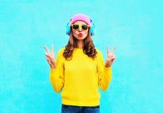 Manier vrij koel meisje die in hoofdtelefoons aan muziek luisteren die kleurrijke roze hoeden gele zonnebril en sweater over blau royalty-vrije stock afbeeldingen