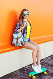 Manier vrij koel meisje die zonnebril met skateboard dragen royalty-vrije stock afbeeldingen