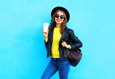 Manier vrij onbezorgde glimlachende vrouw met koffiekop die kleren van een de zwarte rotsstijl over kleurrijk blauw dragen Royalty-vrije Stock Afbeeldingen