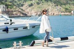 Manier whilte uitrusting van in mooie lachende vrouw in zonnebril die op de witte jachtachtergrond stellen stock afbeelding