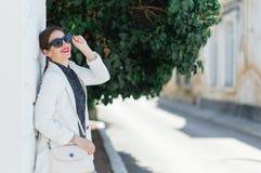 Manier whilte uitrusting van in mooie lachende vrouw in zonnebril die op de witte muurachtergrond stellen stock afbeelding