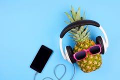 Manierananas met zonnebril en hoofdtelefoons over blauw Royalty-vrije Stock Afbeeldingen