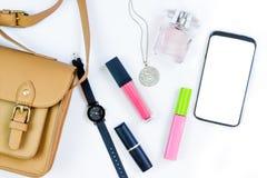 Manierconcept: de vrouwen doen met schoonheidsmiddelen, toebehoren en een smartphone op een witte achtergrond in zakken Vlak leg, stock afbeelding