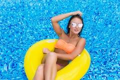 Manierfoto van sexy mooi Meisje in gele bovenkant en zonnebril ontspannen die op opblaasbare ring drijven In openlucht levensstij stock afbeelding
