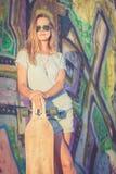 Manierlevensstijl, Mooie jonge blondevrouw met skateboard Royalty-vrije Stock Afbeelding