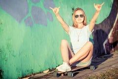 Manierlevensstijl, Mooie jonge blondevrouw met skateboard Royalty-vrije Stock Fotografie