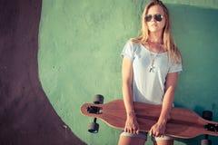 Manierlevensstijl, Mooie jonge blondevrouw met skateboard Royalty-vrije Stock Foto's
