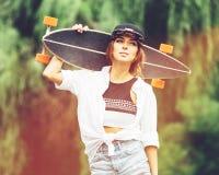 Manierlevensstijl, mooie jonge vrouw met longboard Stock Fotografie