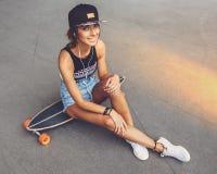 Manierlevensstijl, mooie jonge vrouw met longboard royalty-vrije stock afbeeldingen