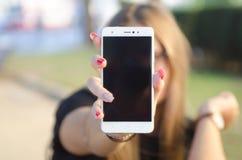 Maniermeisje met rode spijkers, die smartphone tonen stock afbeeldingen