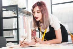 Manierontwerper die aan schets in de studio van het kledingsontwerp werken royalty-vrije stock foto