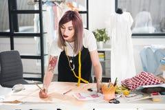 Manierontwerper die aan schets in de studio van het kledingsontwerp werken Royalty-vrije Stock Afbeeldingen