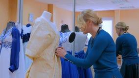 Manierontwerper die met nieuwe model het maken kleding aan ledenpop werken stock footage