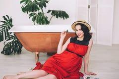 Manierportret van aantrekkelijke modieuze zwangere dame in lange rood sarafan en strohoed, foto van gelukkig en mooi royalty-vrije stock foto