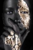 Manierportret van een donker-gevild meisje met goud royalty-vrije stock afbeelding