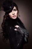 Manierportret van een donkerbruine vrouw in zwarte kleren stock foto