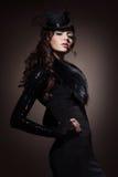 Manierportret van een donkerbruine vrouw in zwarte kleren stock foto's