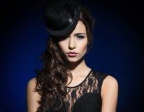 Manierportret van een donkerbruine vrouw in zwarte kleren stock afbeeldingen