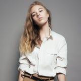 Manierportret van een mooie jonge blondevrouw in een wit overhemd in de studio op een grijze achtergrond Stock Afbeeldingen