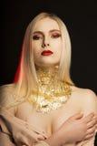 Manierportret van jong model met lang blondehaar en gouden Stock Afbeeldingen