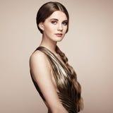 Manierportret van jonge mooie vrouw in gouden kleding Stock Foto's
