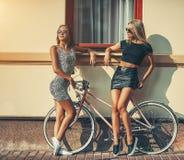 Manierportret van modieuze twee meisjes dichtbij wijnoogst bikycle - uit stock foto