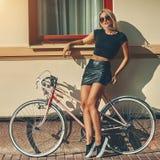 Manierportret van mooi blondemeisje dichtbij uitstekende fiets stock afbeeldingen