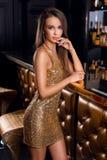 Manierportret van mooi brunette in gouden glanzende kleding met heldere samenstelling royalty-vrije stock foto