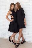 Manierschot van twee mooie meisjes in sexy zwarte kleding tegen een achtergrond van een baksteen witte muur in de studio Stock Foto's