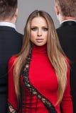Manierspruit van blond meisje in rode kleding en twee kerels in bl Stock Foto's