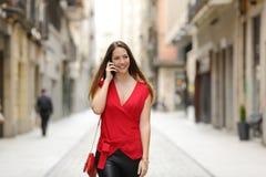 Maniervrouw die en op de mobiele telefoon lopen spreken Royalty-vrije Stock Foto