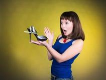 Maniervrouw die hoog-hielschoen bekijken De vrouwen houden schoenen van concept Gillend meisje en hoge hielenschoenen op gele ach Stock Foto's
