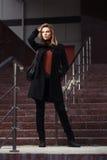 Maniervrouw die in zwarte laag op de straat van de nachtstad lopen Stock Foto's