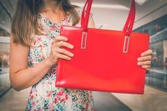 Maniervrouw met rode handtas in winkelcentrum royalty-vrije stock foto