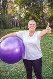 Maniez maladroitement pour l'exercice sain - femme supérieure de sourire avec le fitn photo stock
