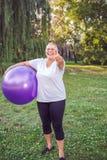 Maniez maladroitement pour l'exercice sain - femme supérieure heureuse avec des fitnes images stock