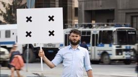 Manifestante adulto joven en el fondo de un coche policía en una reunión con una bandera almacen de video