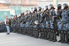 Manifestante desconocido con un cartel en el fondo de las filas de la policía Foto de archivo