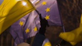 Manifestante femenino que sostiene ucraniano y banderas de la UE como símbolo de la solidaridad metrajes