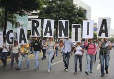 Manifestantes antis de Nicolas Maduro que marchan en una demostración masiva contra el dictatorshi fotografía de archivo
