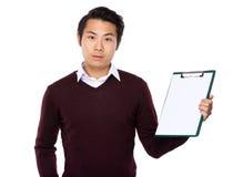 Manifestazione asiatica del giovane con la pagina in bianco della lavagna per appunti Fotografia Stock